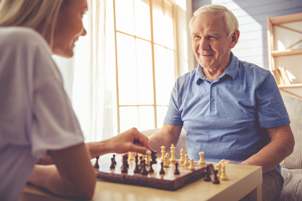 we salute you volunteer playing chess with client geriatric volunteer manager Our care volunteer program Endless Journey Hospice Omaha Nebraska active duty