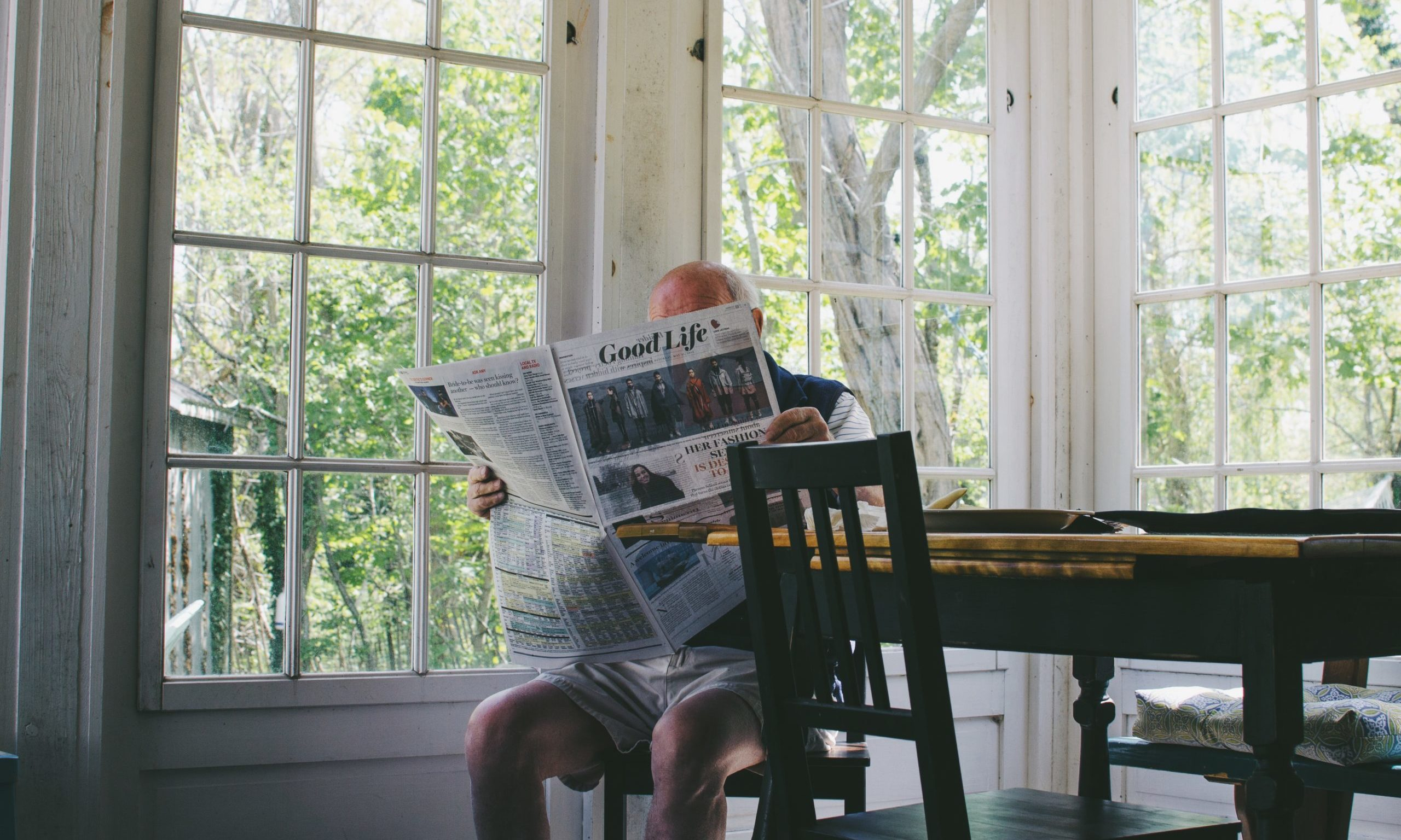 Elderly man reading a newspaper in dinning room our clients Endless Journey Hospice Omaha Nebraska
